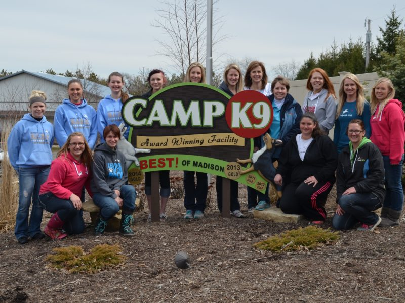CampK9 award winning facility sign with the Camp K9 team posed around it.