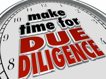 "A clock with the phrase, ""Make time for due diligence,"" written on it in black and red letters."