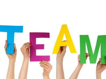 """Six hands hold up blue, magenta, yellow, and green letters that spell out the word """"team."""""""