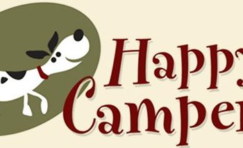 """A beige, green, and red banner with a cartoon dog wagging its tail that reads, """"Happy Camper."""""""