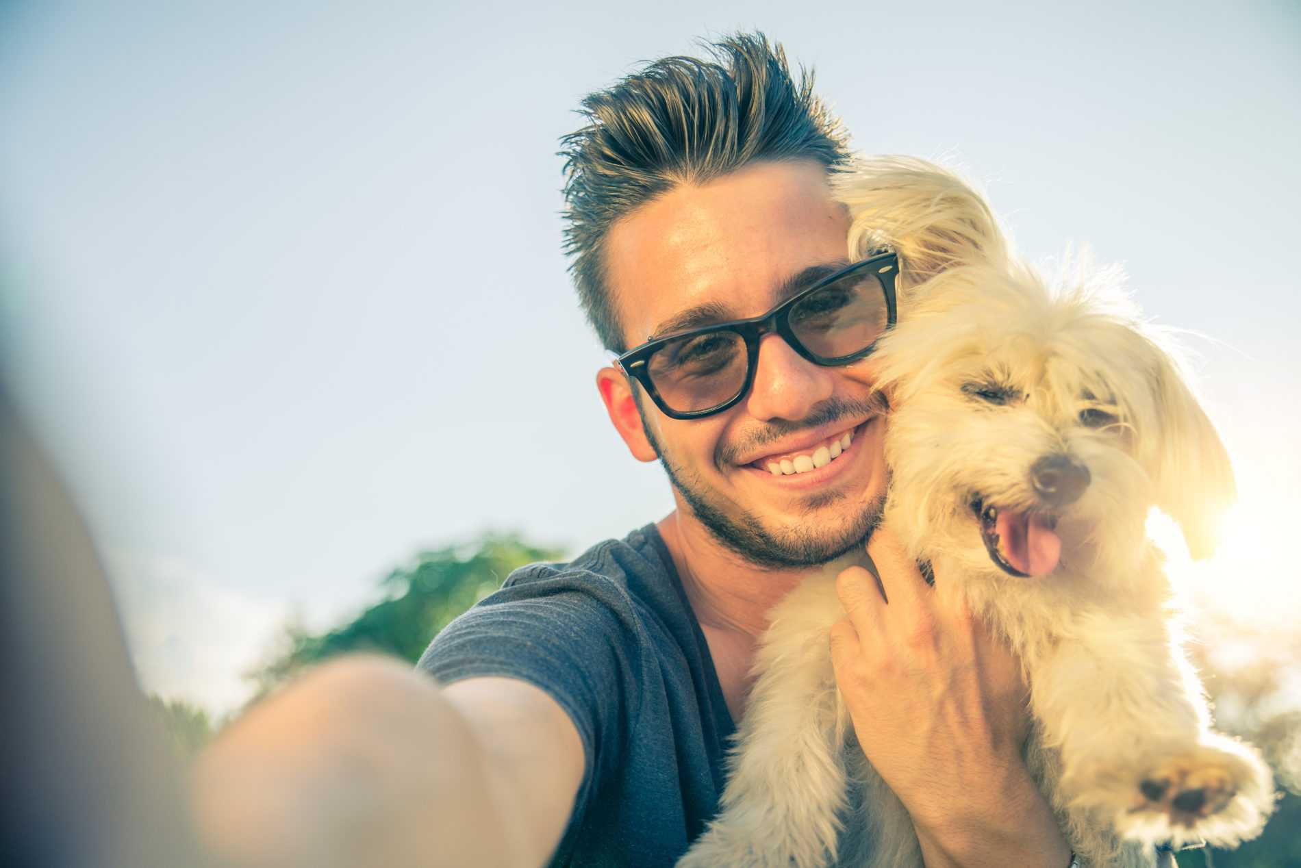 Man in black rimmed glasses holding up a small dog and taking a selfie with the sun shining behind them.